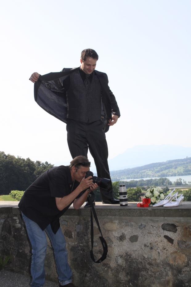 Bräutigam sorgt für Schatten, damit das Licht für den Fotografien stimmt.